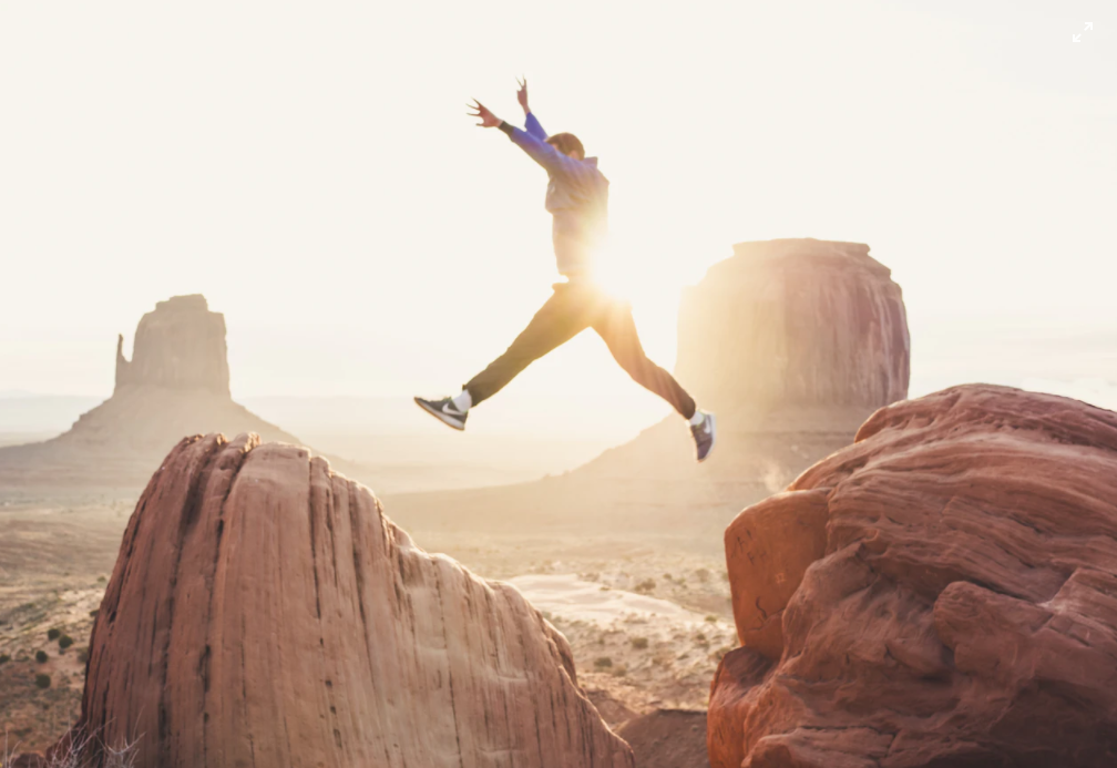 A man leaping from one rock to another with his arms in the air